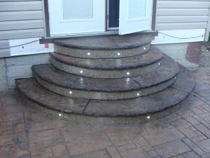Decorative stamped concrete steps with lights on