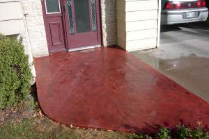 Red stamped decorative concrete front door driveway
