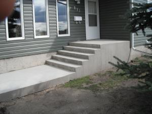 Concrete steps and sidewalk beside house